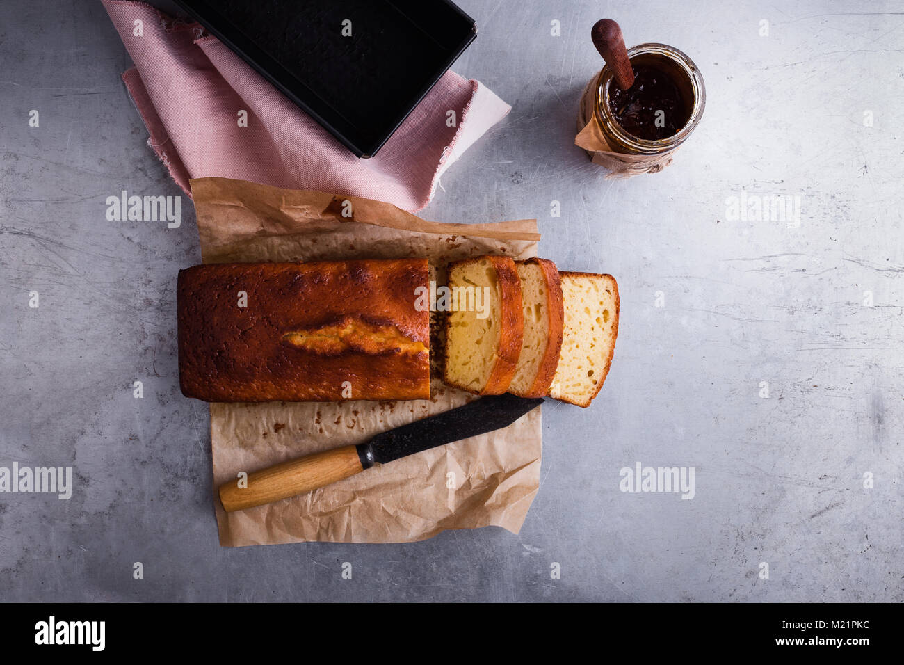 Homemade pound cake on baking paper served with fruit jam ready to eat, top view - Stock Image