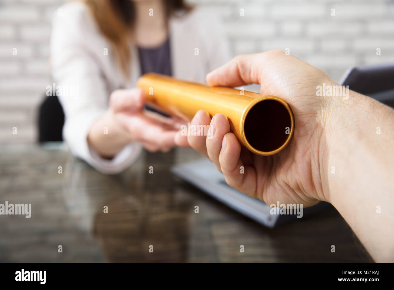 Close-up Of A Hand Passing Golden Relay Baton To Businesswoman - Stock Image