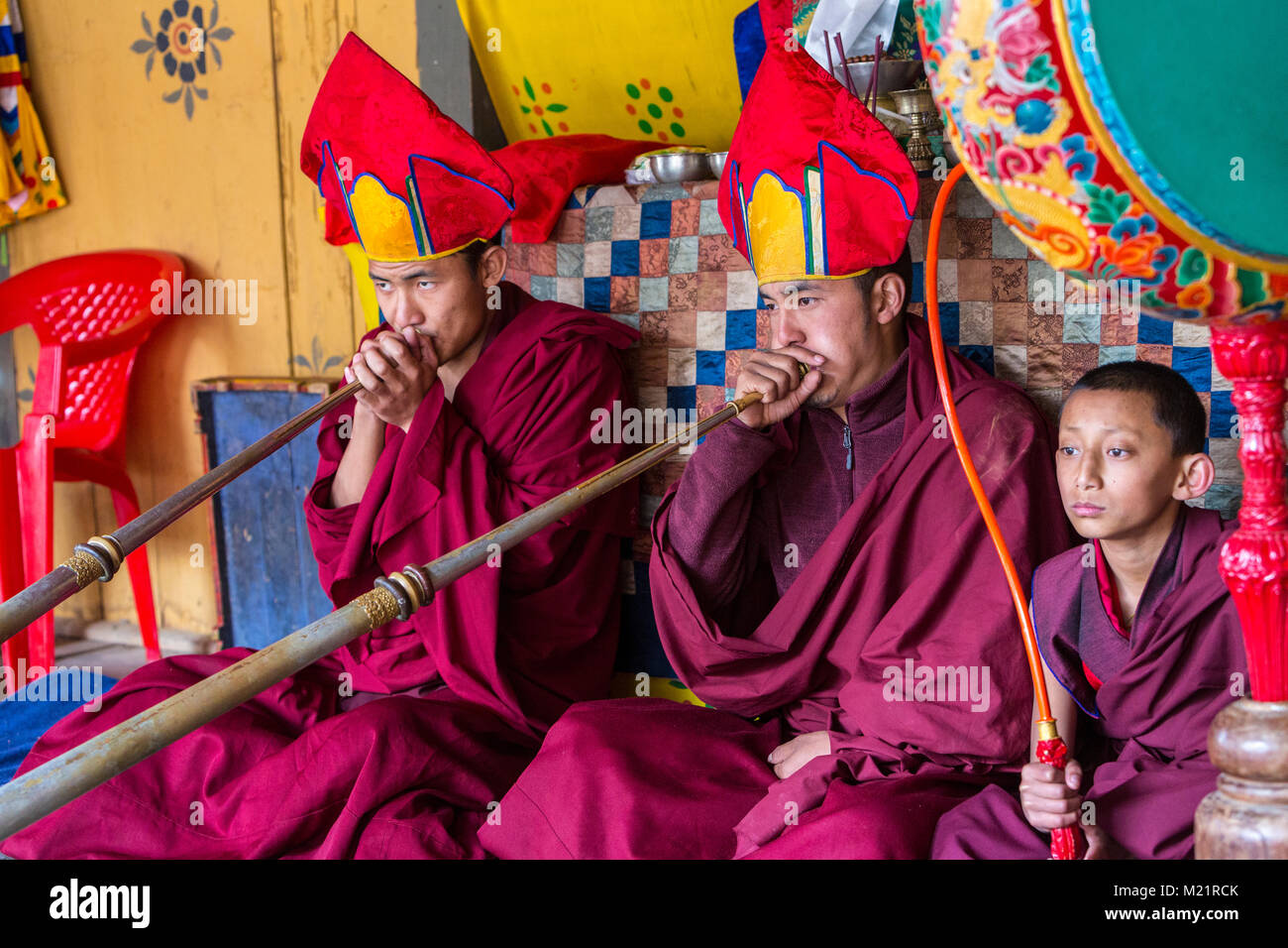 Prakhar Lhakhang, Bumthang, Bhutan.  Buddhist Monks Playing the Dungchen (Long Trumpet), Young Monk Playing the - Stock Image
