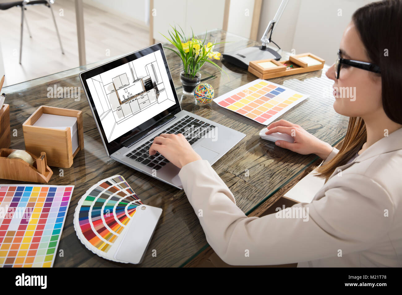 An Female Architect Working On Color Selection For The Kitchen Drawing On Laptop Screen Stock Photo