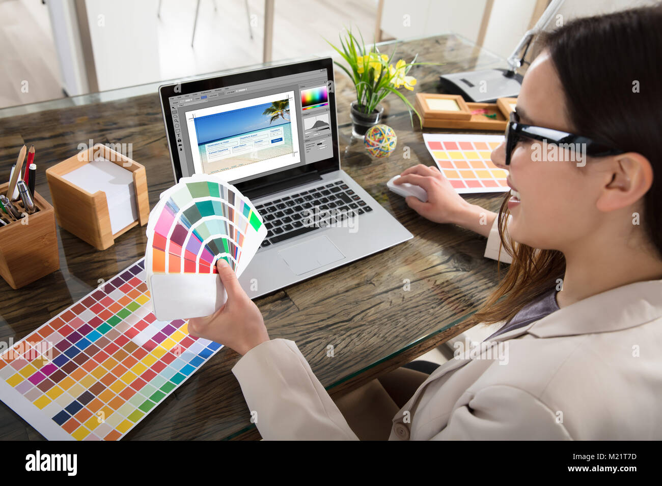 A Female Designer Using Laptop While Holding Colour Swatches In Her Hand - Stock Image