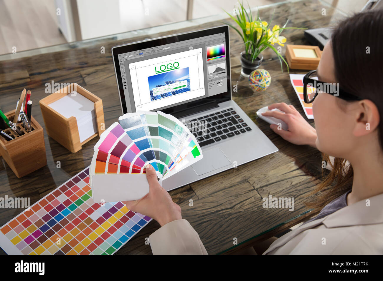 A Woman Holding Color Swatches Using A Laptop With Logo Design Software On The Screen Stock Photo