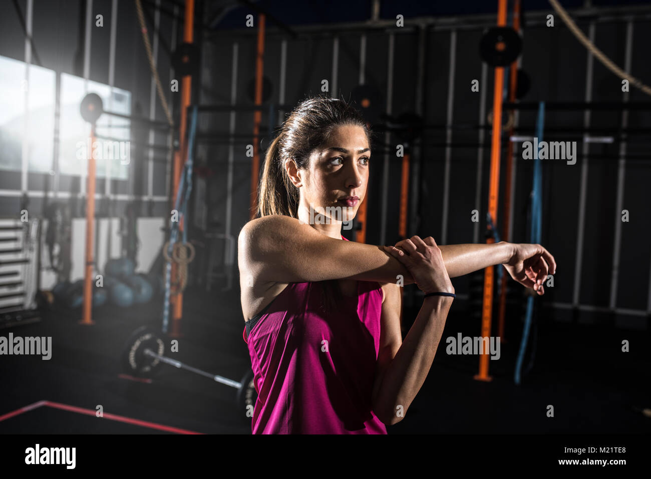 Athletic girl does stretching exercises at the gym - Stock Image