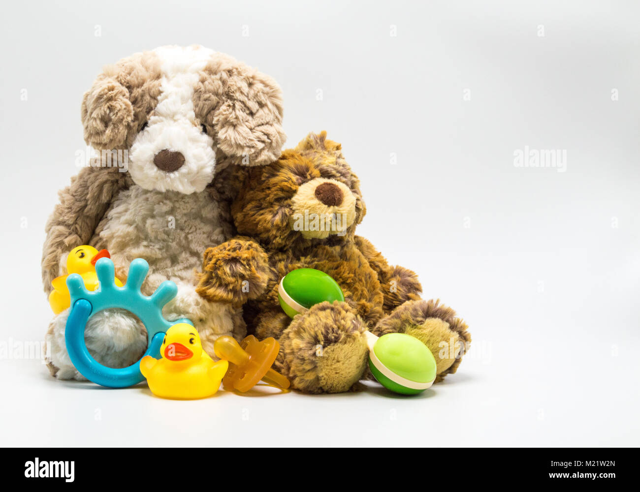 2 plush brown teddy bears with a baby rattle, teething ring, pacifier and 2 rubber ducks isolated on a solid background - Stock Image