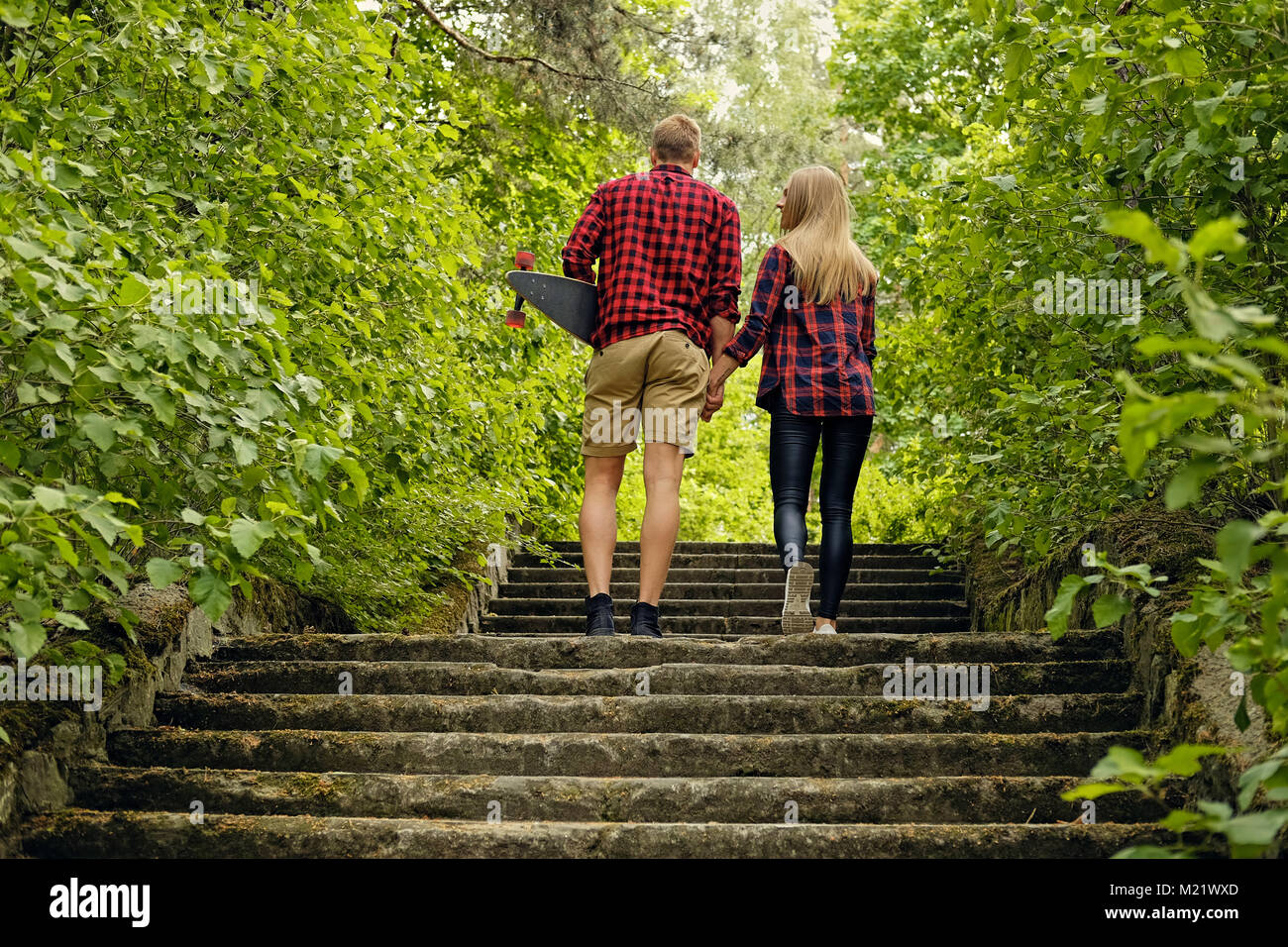 Skateboarders couple to go upstairs in nature parks. Stock Photo
