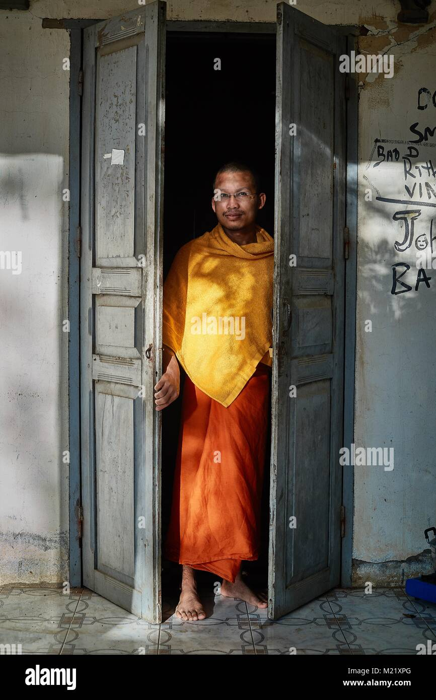 Buddhist Monk at door of monastry rooms, Battambang, Cambodia - Stock Image