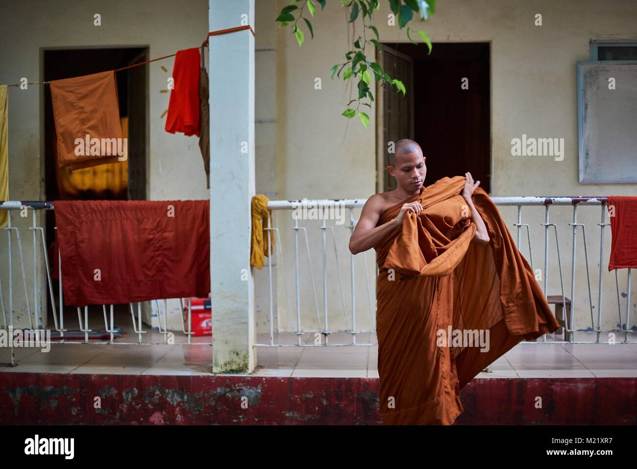 Buddhist Monk in front of monastry rooms, Battambang, Cambodia - Stock Image