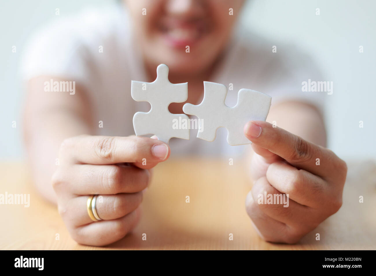 Asian woman jointing jigsaw puzzle shallow depth of field select focus on hands - Stock Image