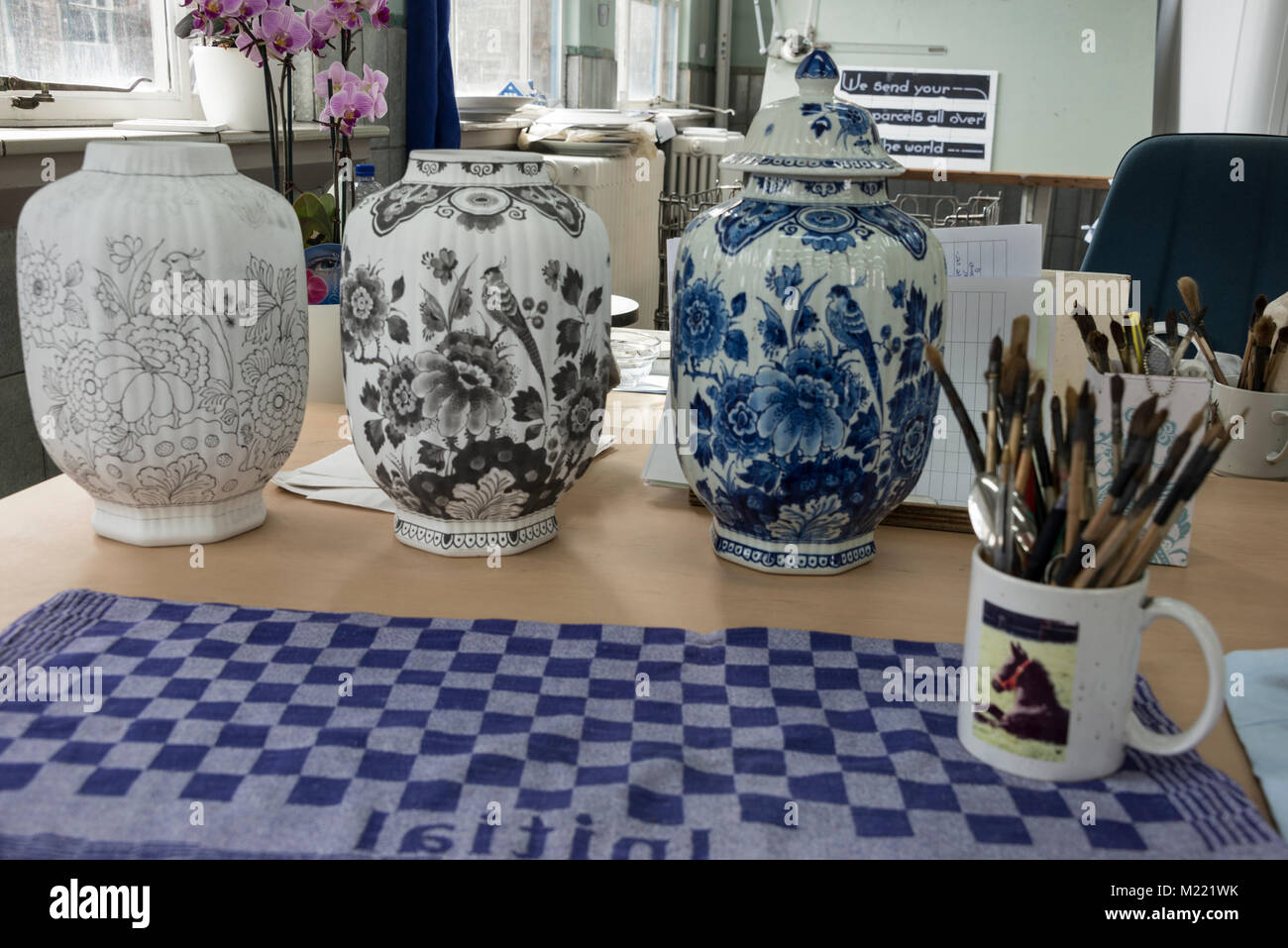 Three vases at the world's famous Delftware factory: Royal Delft in Delft, Holland.  1st vase drawn the outlines - Stock Image