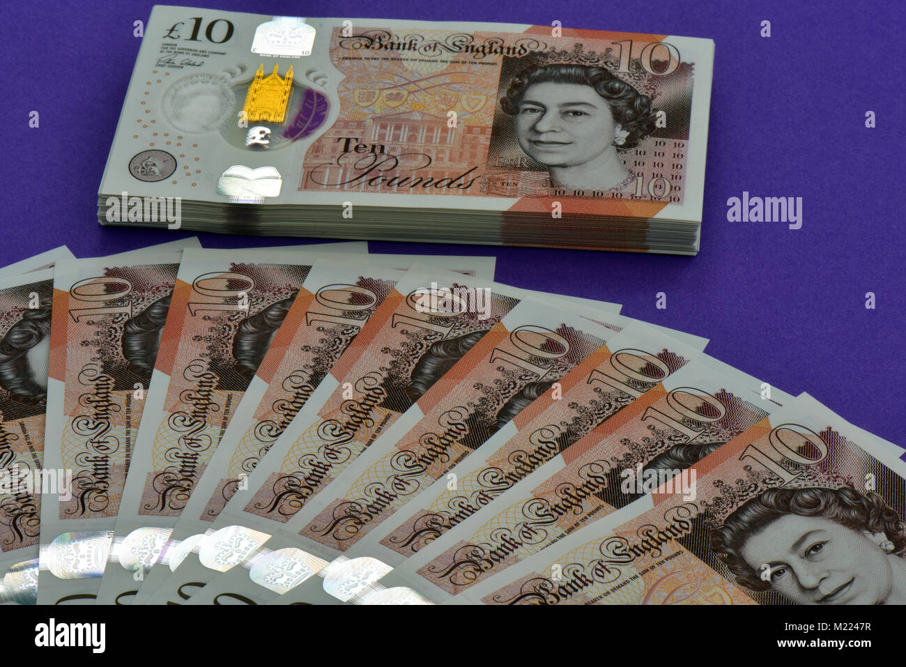 a pile or wad of ten pound notes next to a fan of notes laid onto a flat lilcac coloured  surface. Money in notes - Stock Image