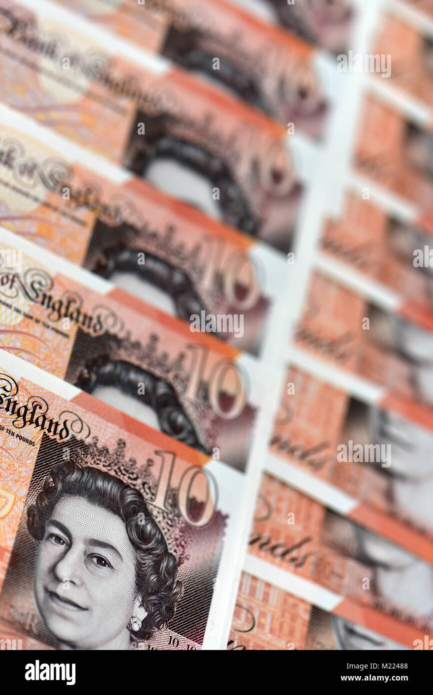 a lot or number of ten pound notes laid out in rows or lines on a flat surface or table. ten pounds notes currency - Stock Image