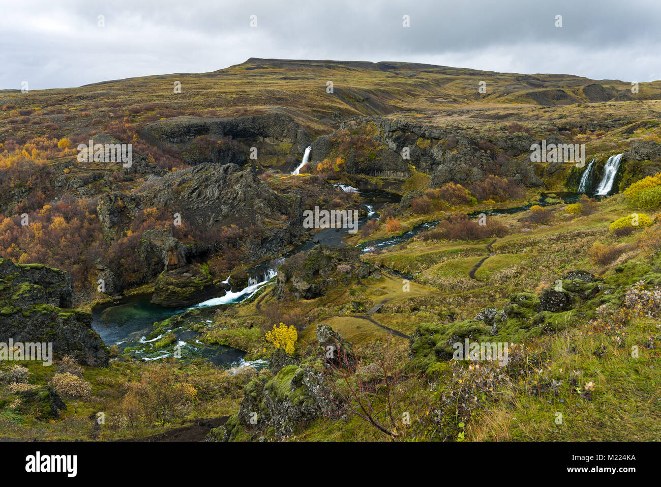Gjainfoss waterfall in the Gjain valley of the Highlands of Iceland in Autumn colours on a cloudy day, Iceland - Stock Image