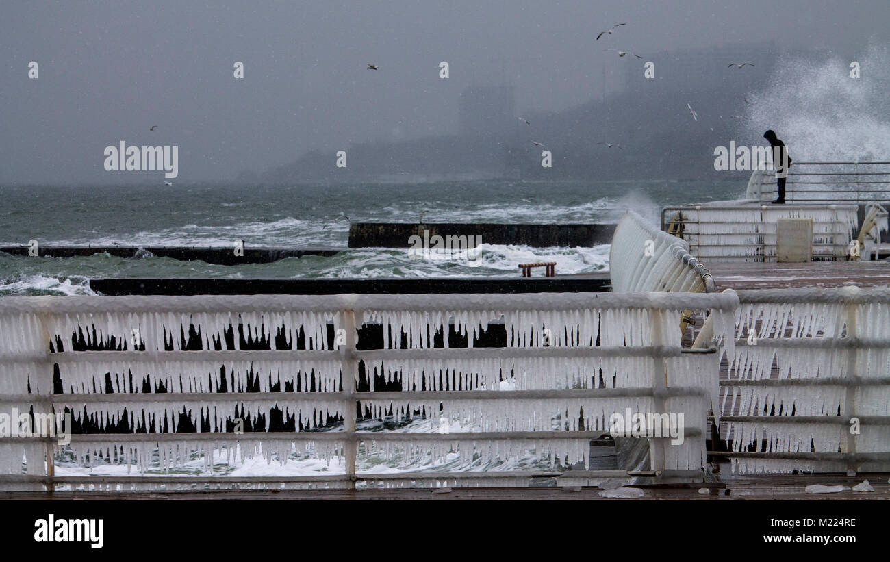 Winter storm raging over Black Sea near Odessa coast (Ukraine) and a lonely figure of a man on a frozen quay Stock Photo
