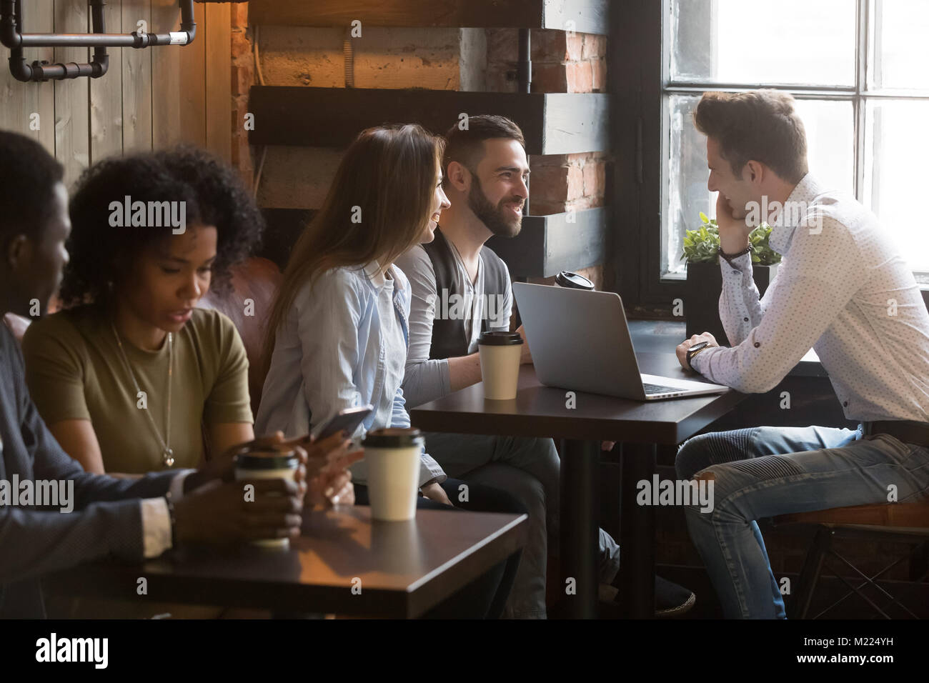 Diverse multiracial young people talking drinking coffee in cozy - Stock Image