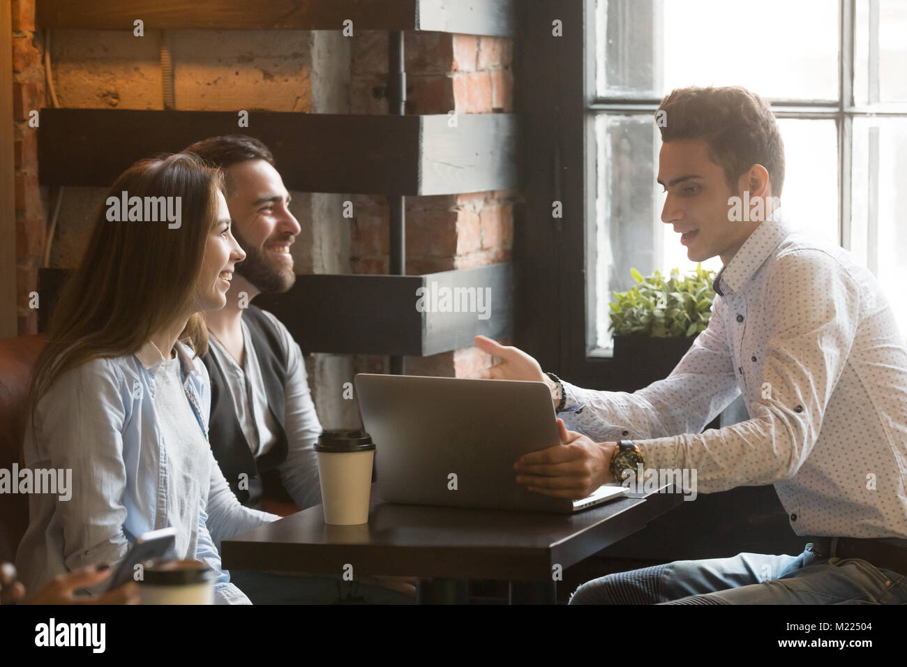Insurance broker or salesman making offer to couple in cafe - Stock Image