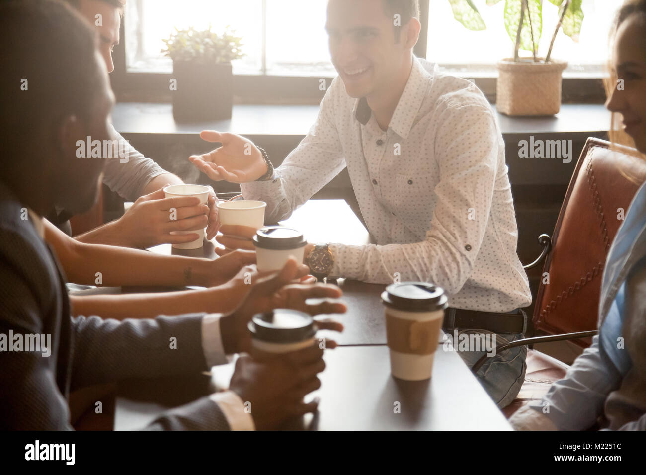 Multi ethnic group of friends drinking coffee together in cafe - Stock Image
