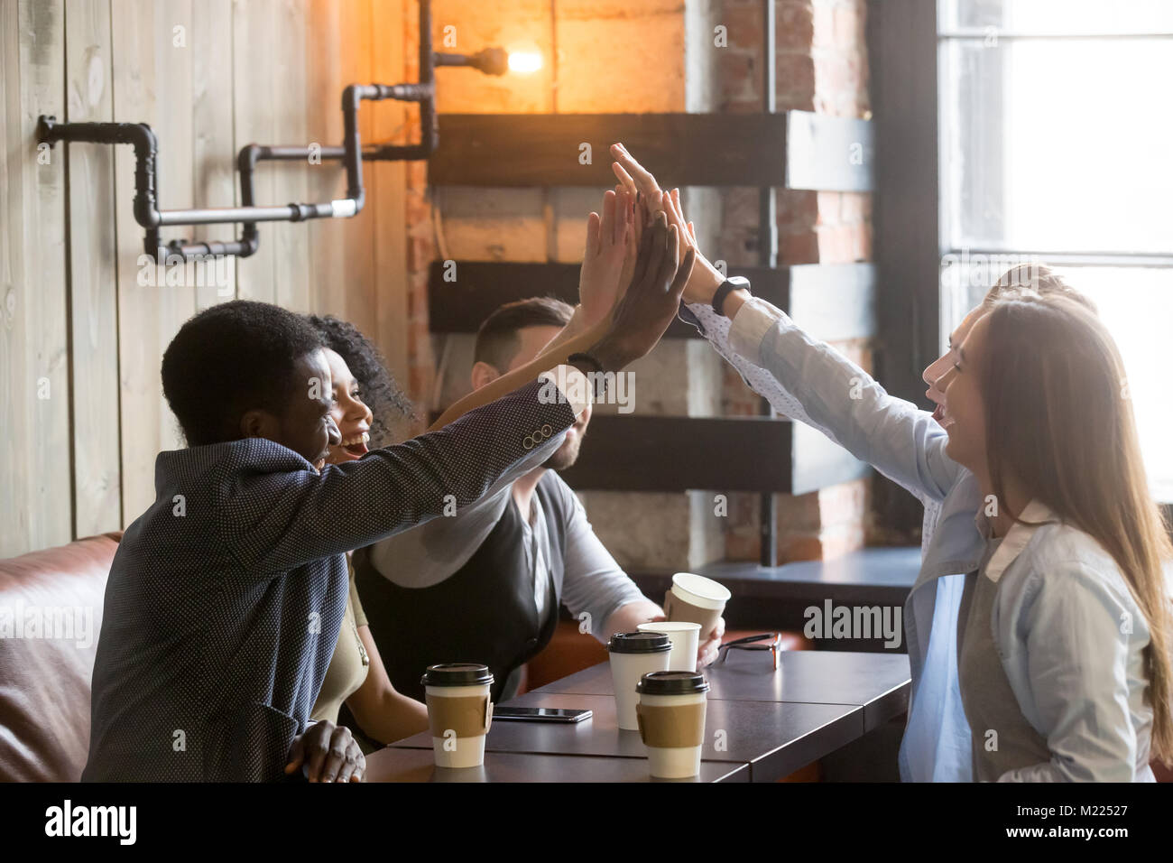 Diverse friends join hands together giving high-five at cafe mee - Stock Image