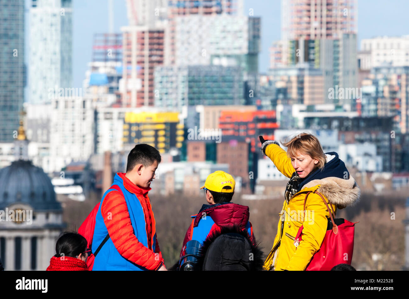 A school party,  at Greenwich Park looking at building work on the Isle of Dogs (oof). - Stock Image