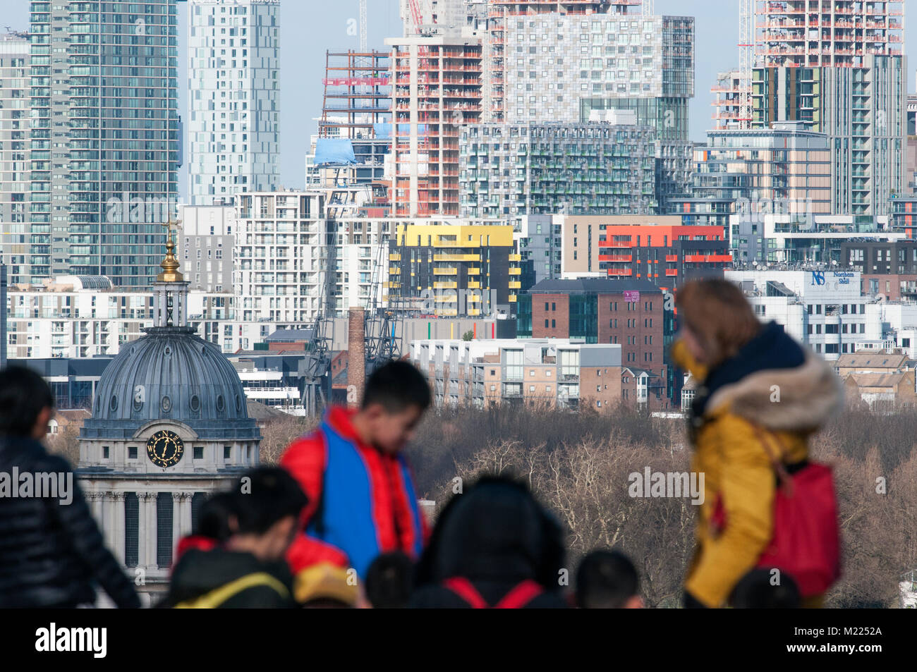 A school party, oof, at Greenwich Park in front of building work on the Isle of Dogs. - Stock Image