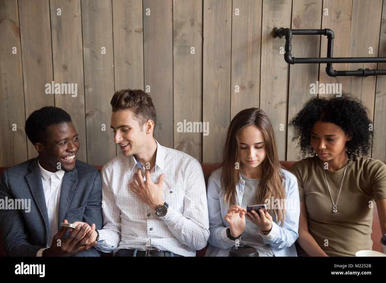 Millennial multiracial friends using mobile phones and talking a - Stock Image
