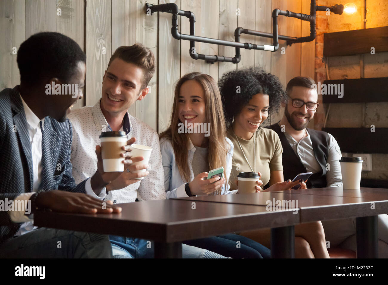 Happy multi-ethnic group of friends talking using smartphones at - Stock Image
