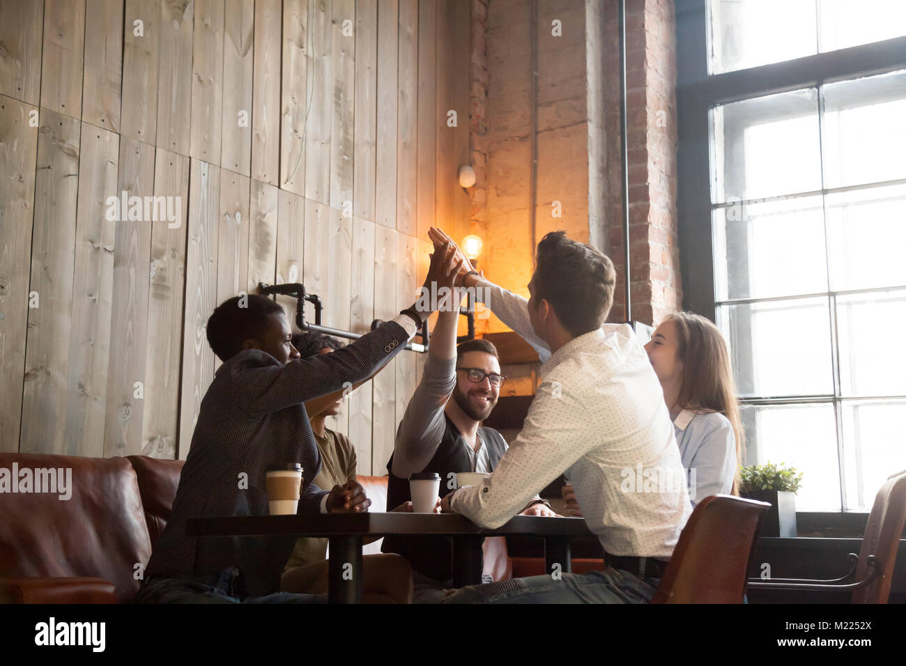 Multiracial friends group giving high five sitting at cafe table - Stock Image
