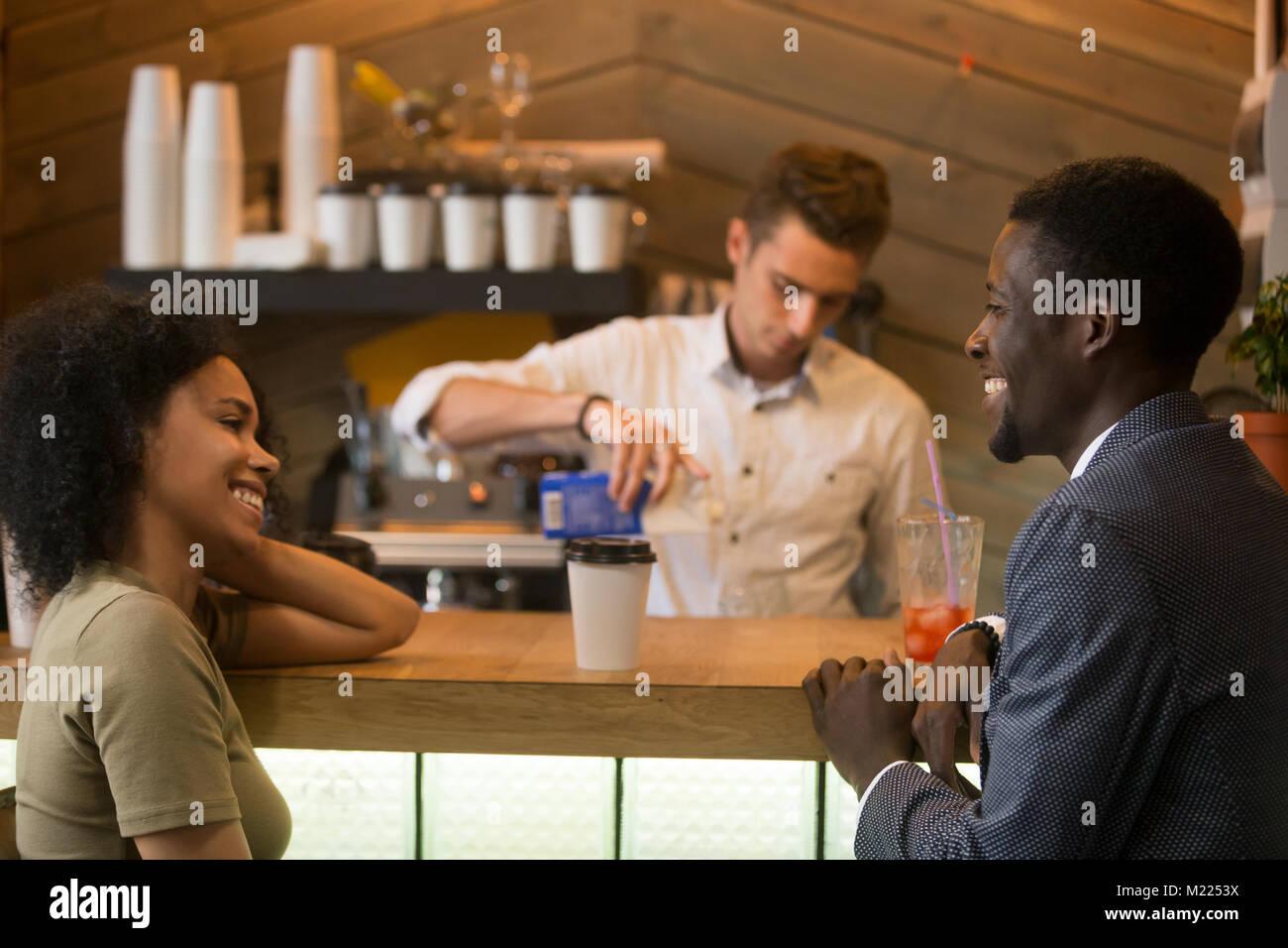 African-american man and woman flirting talking at coffeeshop ba - Stock Image