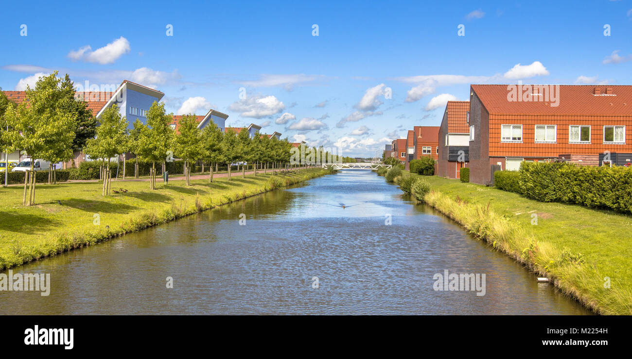 River in modern suburb neigborhood with houses along ecological park Stock Photo