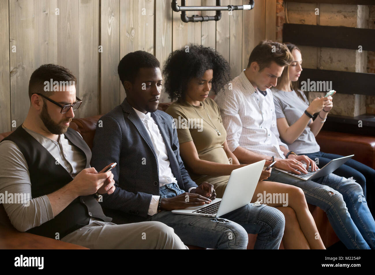 Multiracial black and white people sitting on couch using device - Stock Image