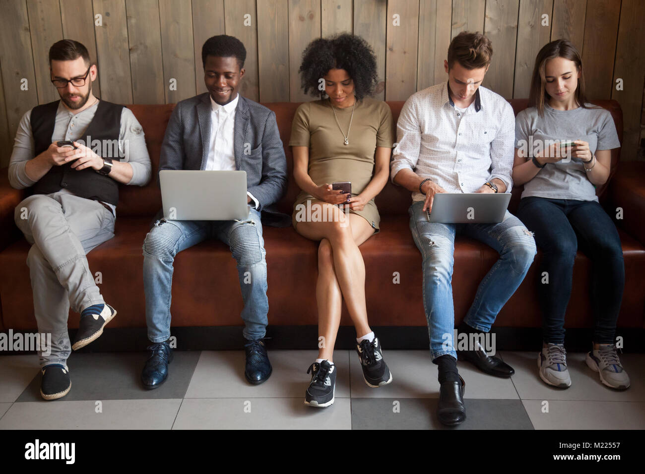 Multicultural young people using laptops and smartphones sitting - Stock Image