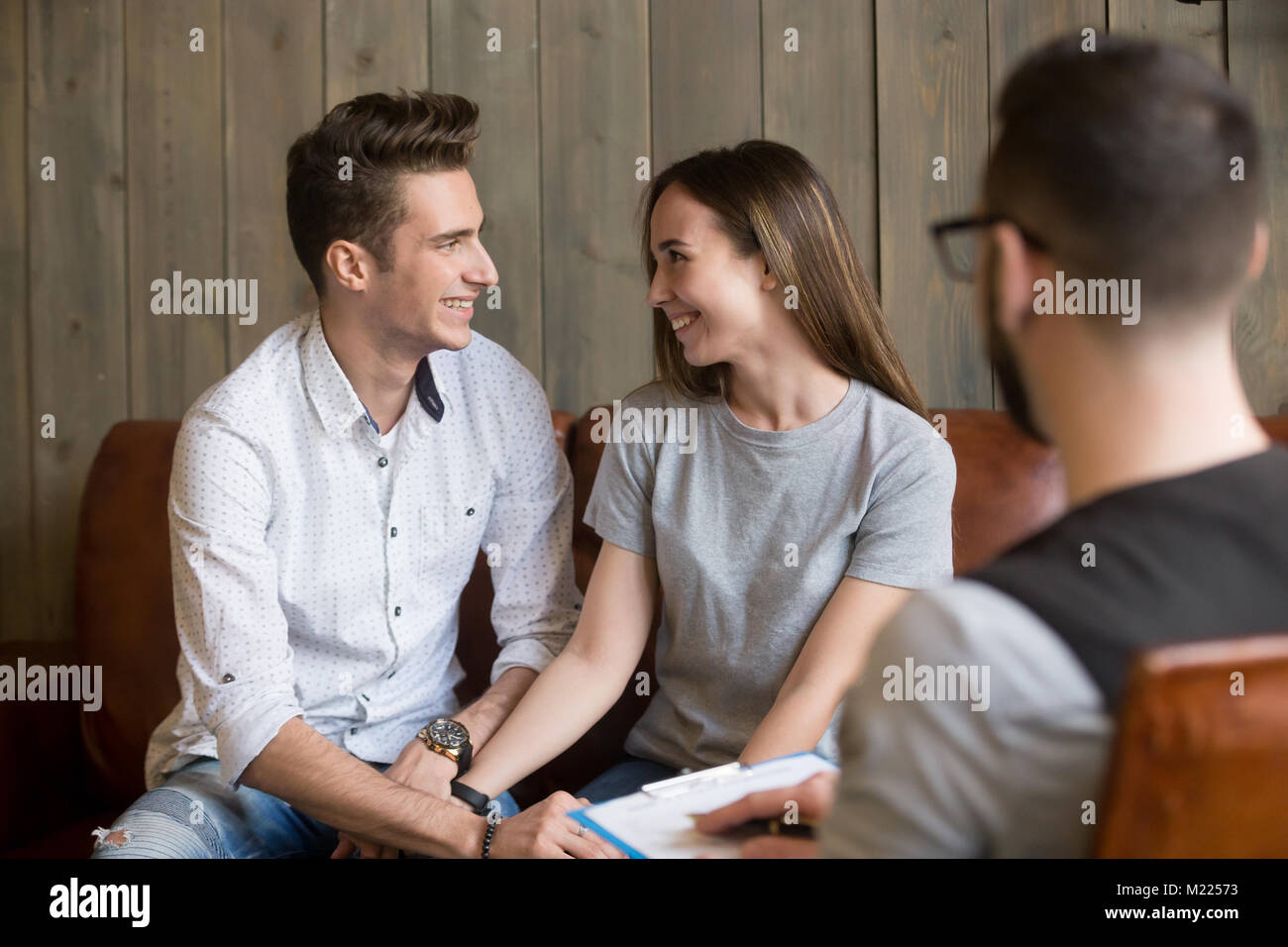 Happy young reconciled couple making up during counseling therap Stock Photo