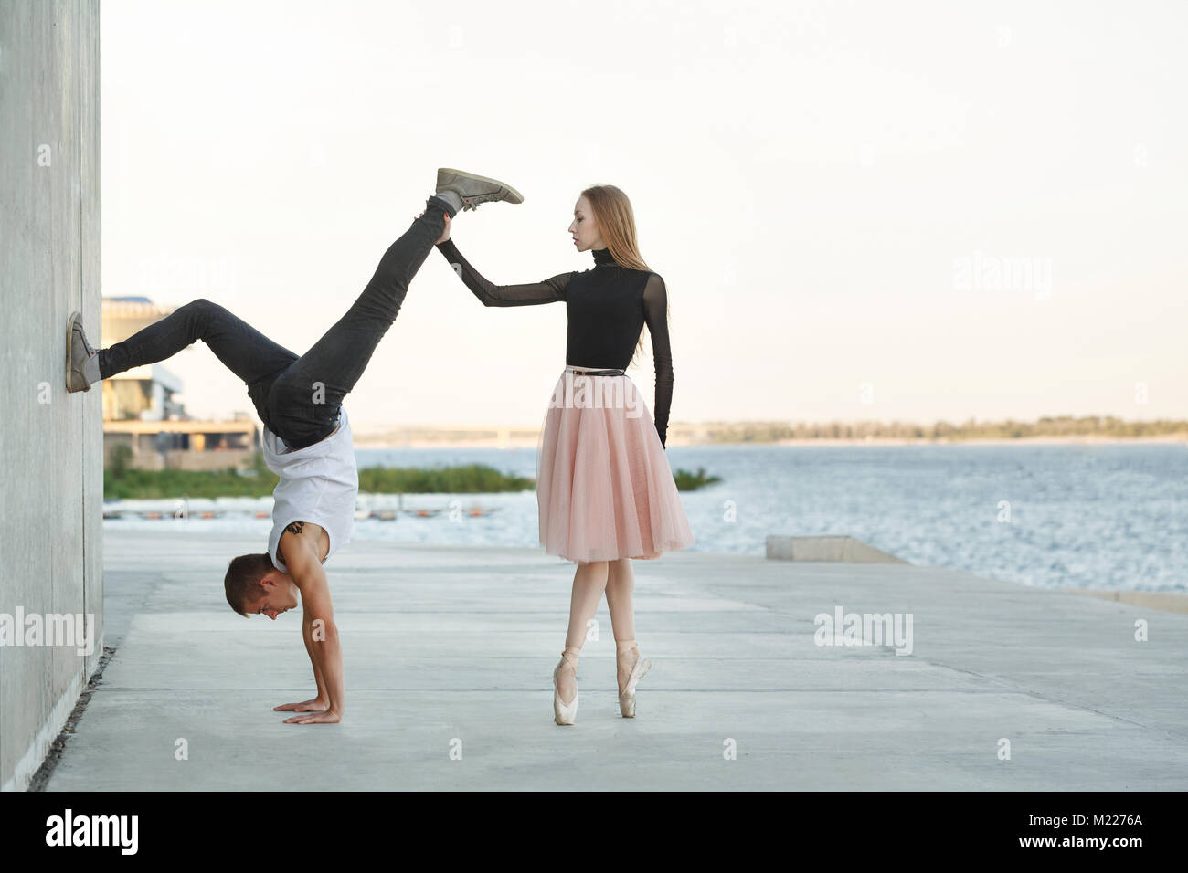 A slender ballerina dances with a modern dancer. Dating lovers. Passion and romance of dance. He stands on his hands. - Stock Image