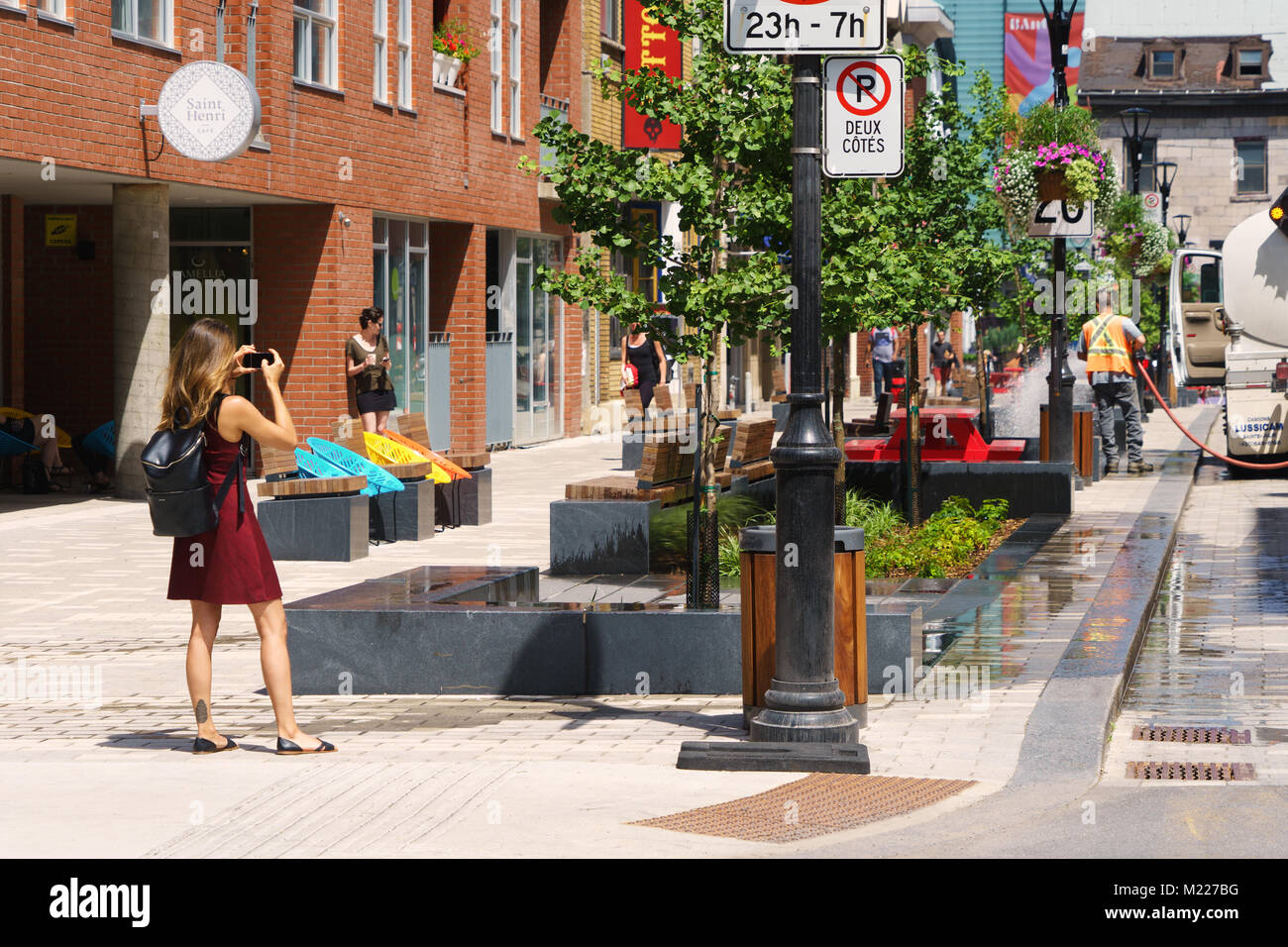 Young woman taking a picture with her smart phone on Emery street, Montreal, province of Quebec, Canada. - Stock Image