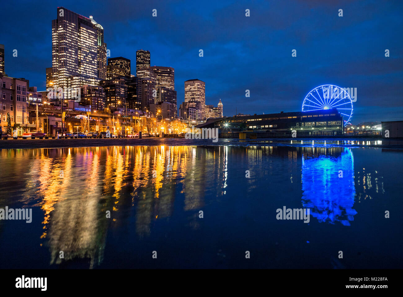 Big Wheel and skyline reflected in puddle of water, Seattle, Washington, USA - Stock Image