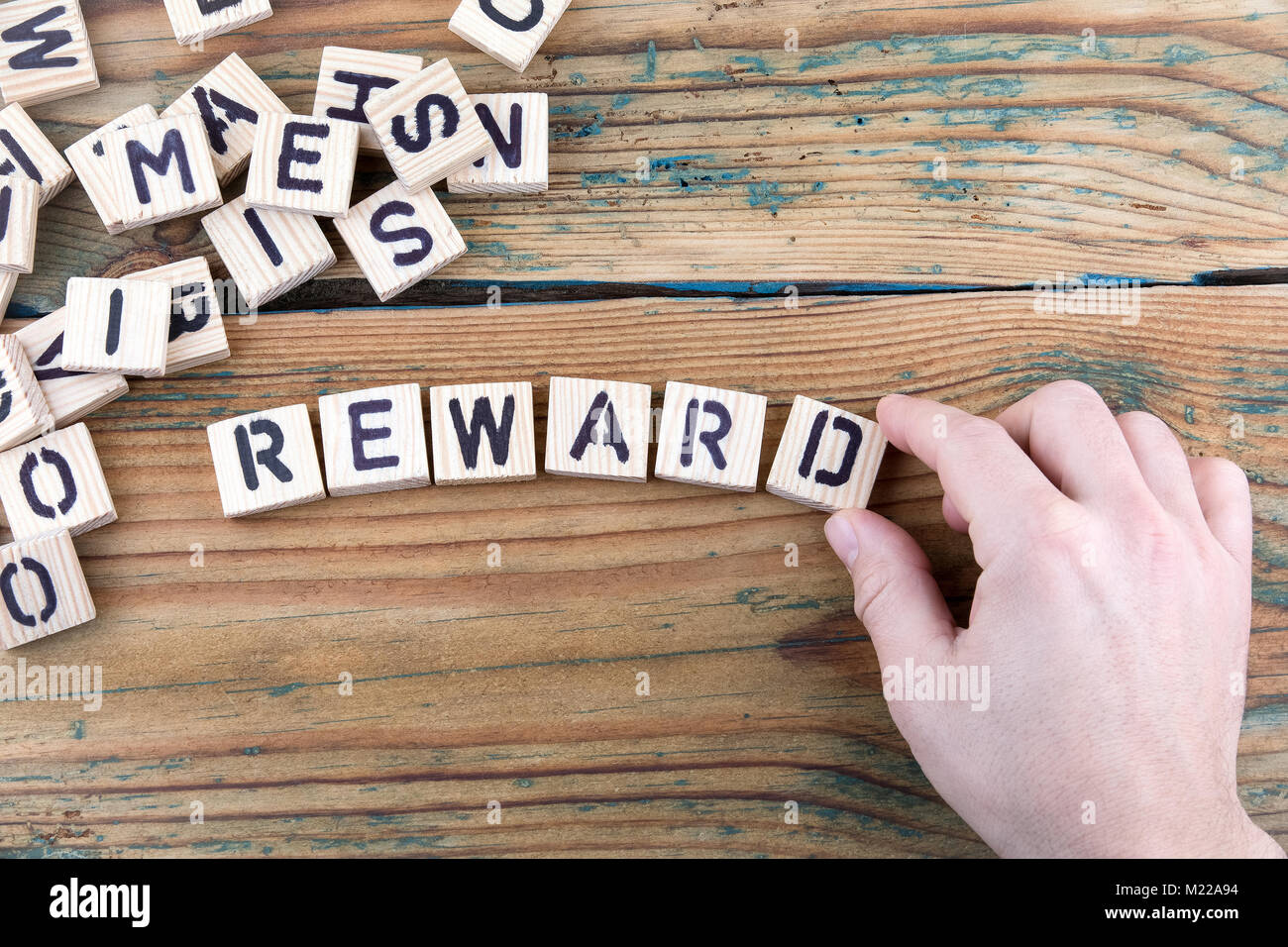 reward. Wooden letters on the office desk, informative and communication background - Stock Image