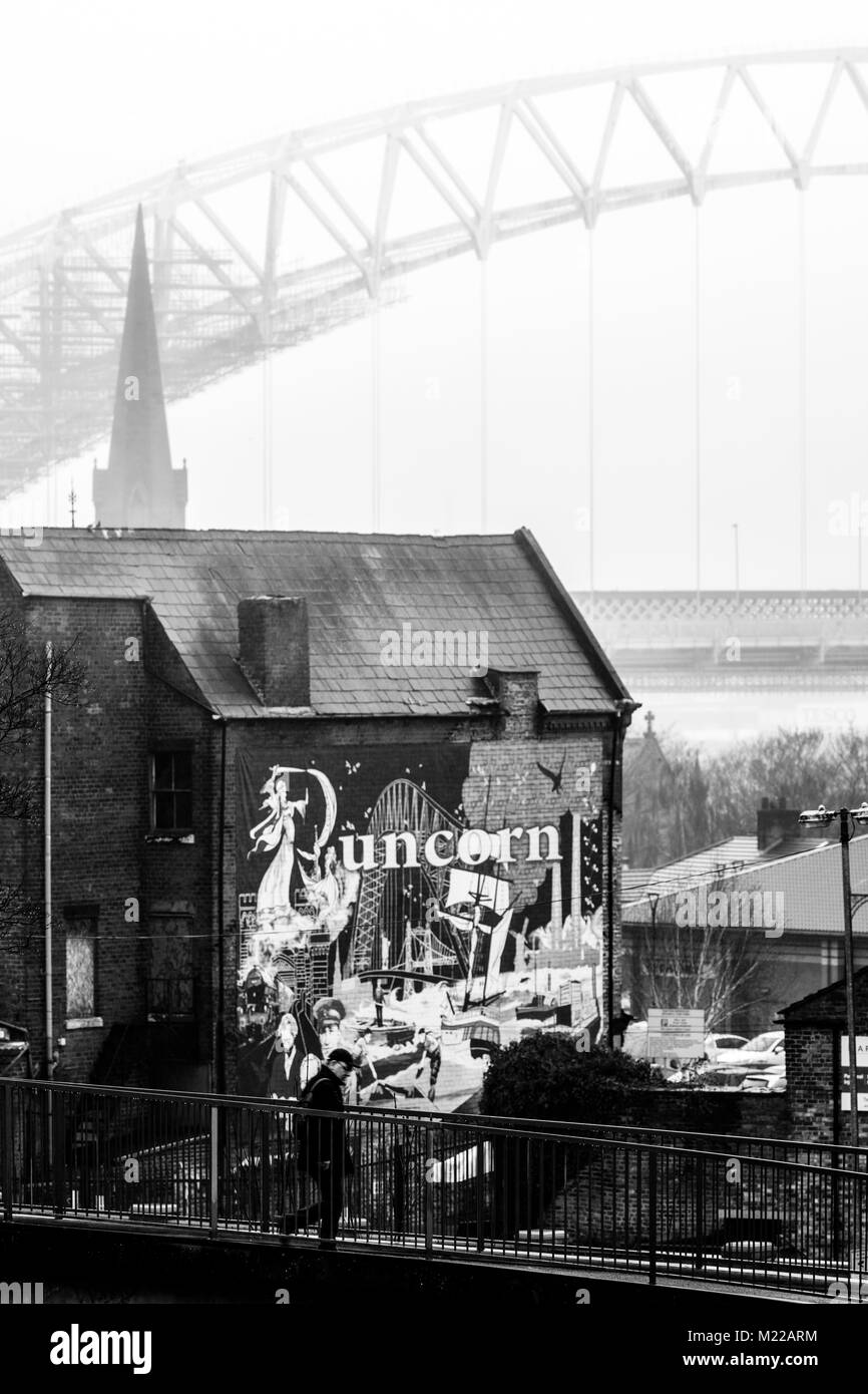 A person walking over a iron bridge across the Bridgewater Canal in the town of Runcorn with mural of Runcorn and - Stock Image