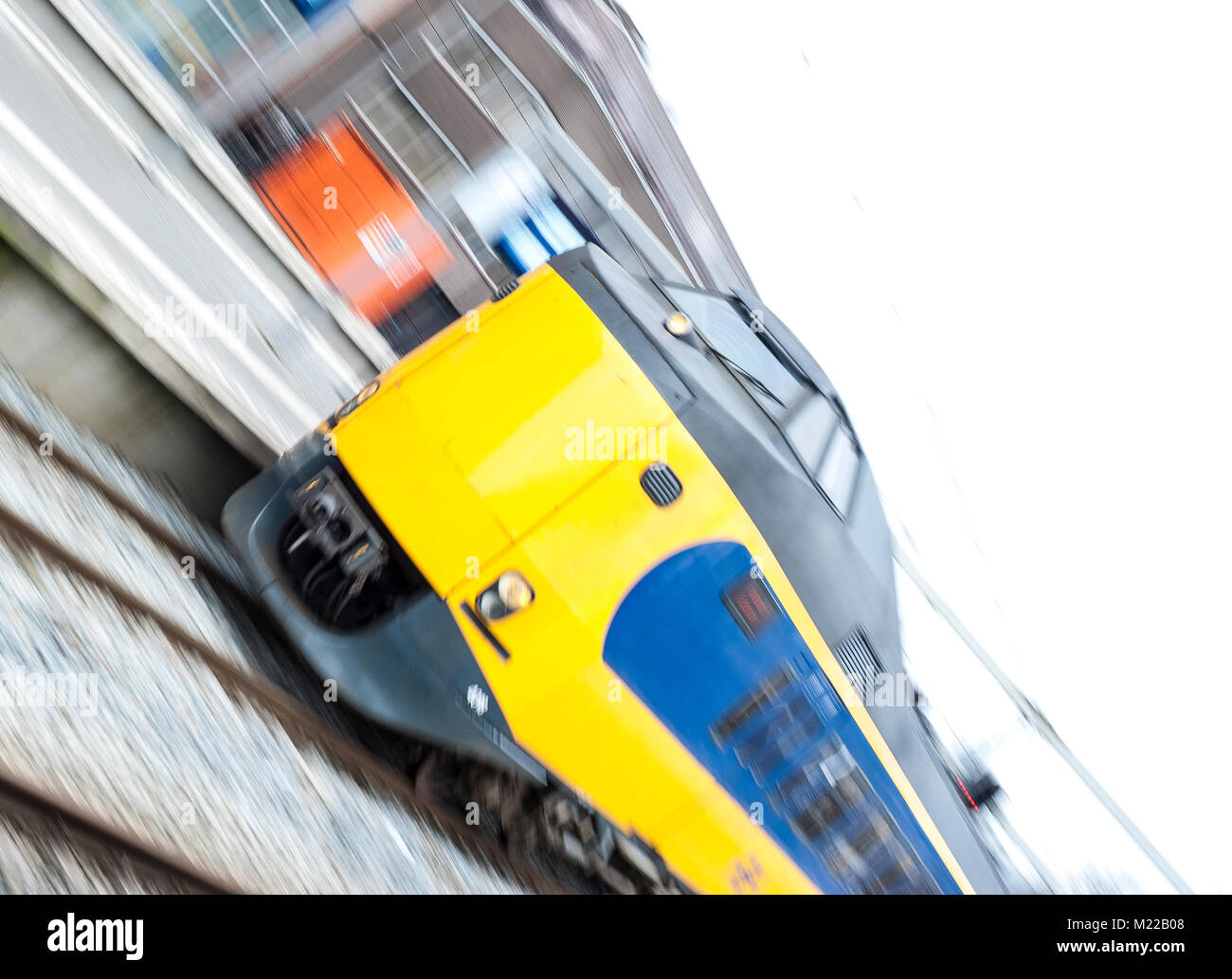 Panning image of a train entering the train station - Stock Image