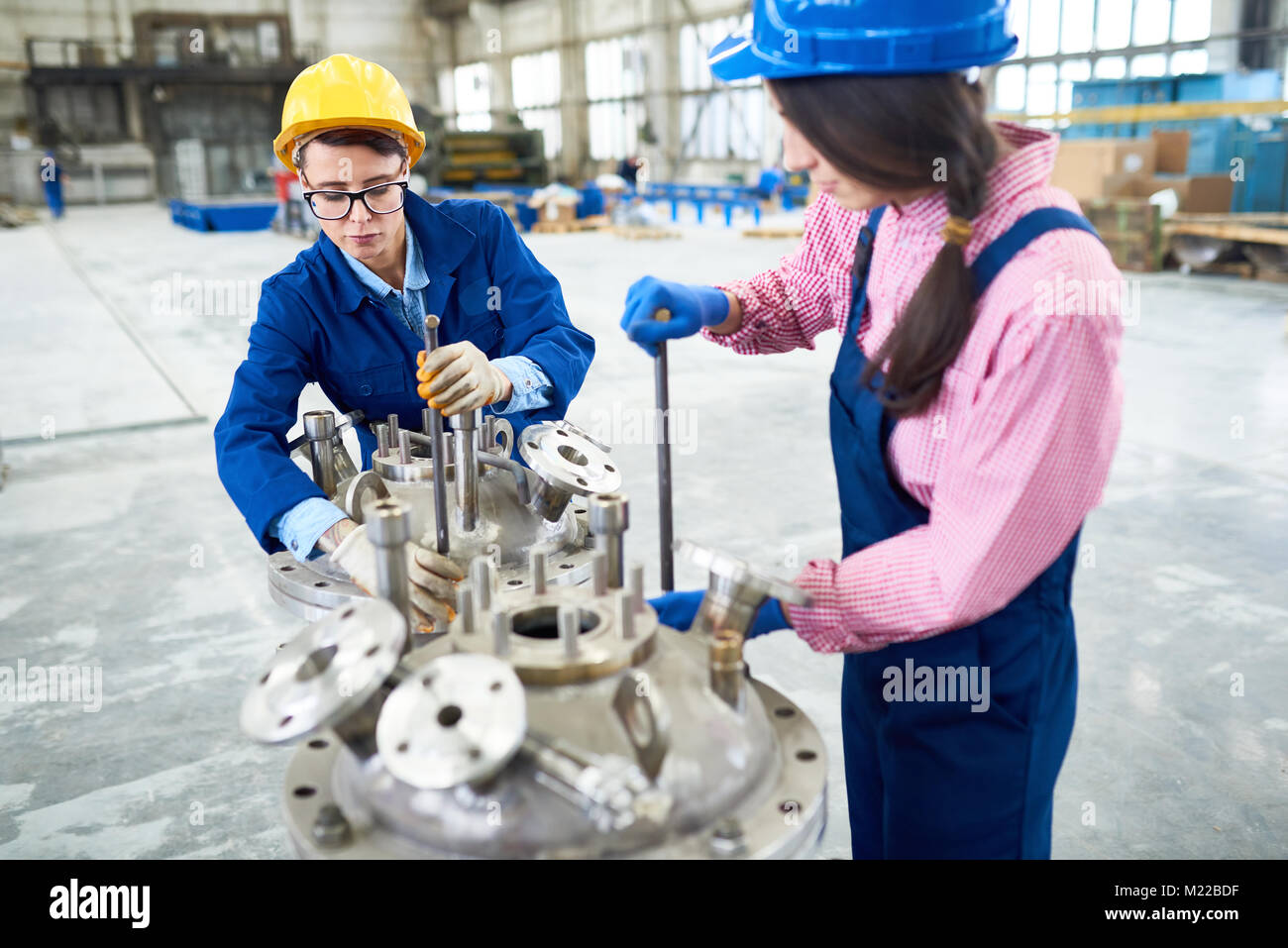 Portrait of two women woman wearing hardhats and uniform working with machine units at modern plant, copy space - Stock Image