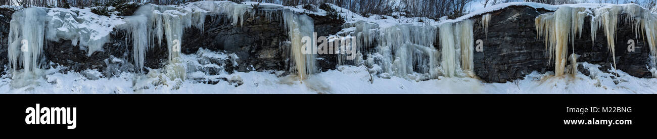 Superwide panorama with icicles hanging from a rock wall in beautiful formations - Stock Image
