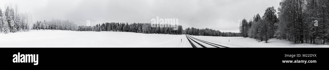 Wide panorama of a road running through a winter landscape - Stock Image