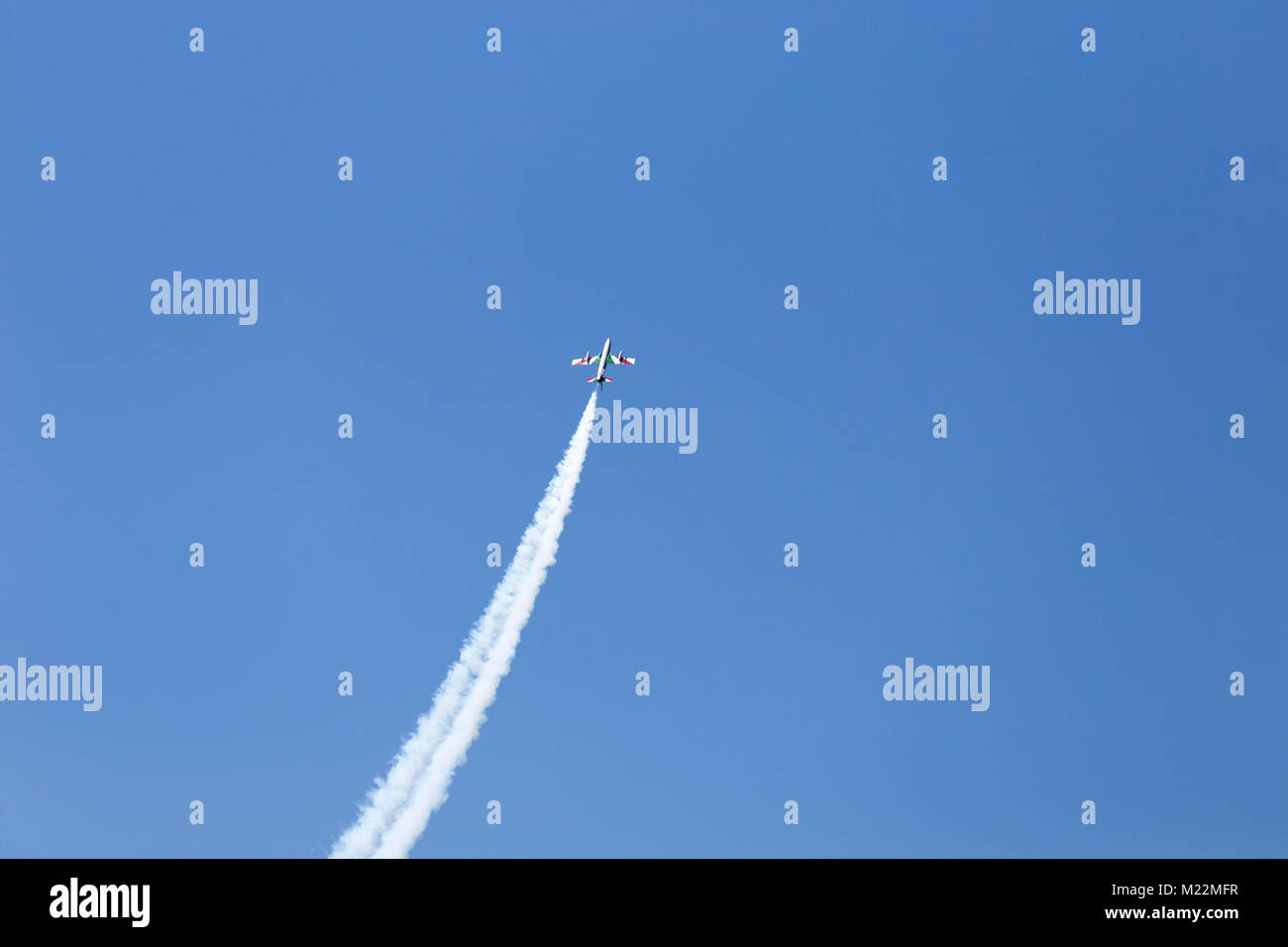 Flight of reactive plane with a lot of smoke - airshow exhibition of solo pilot of Italian acrobatic aircraft team - Stock Image