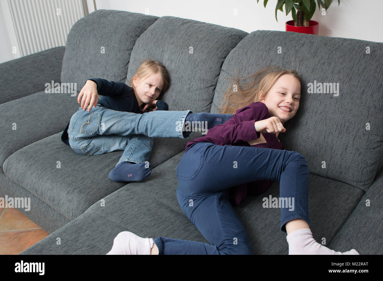 7-year-old girl steps in the back of her 9-year-old sister - Stock Image
