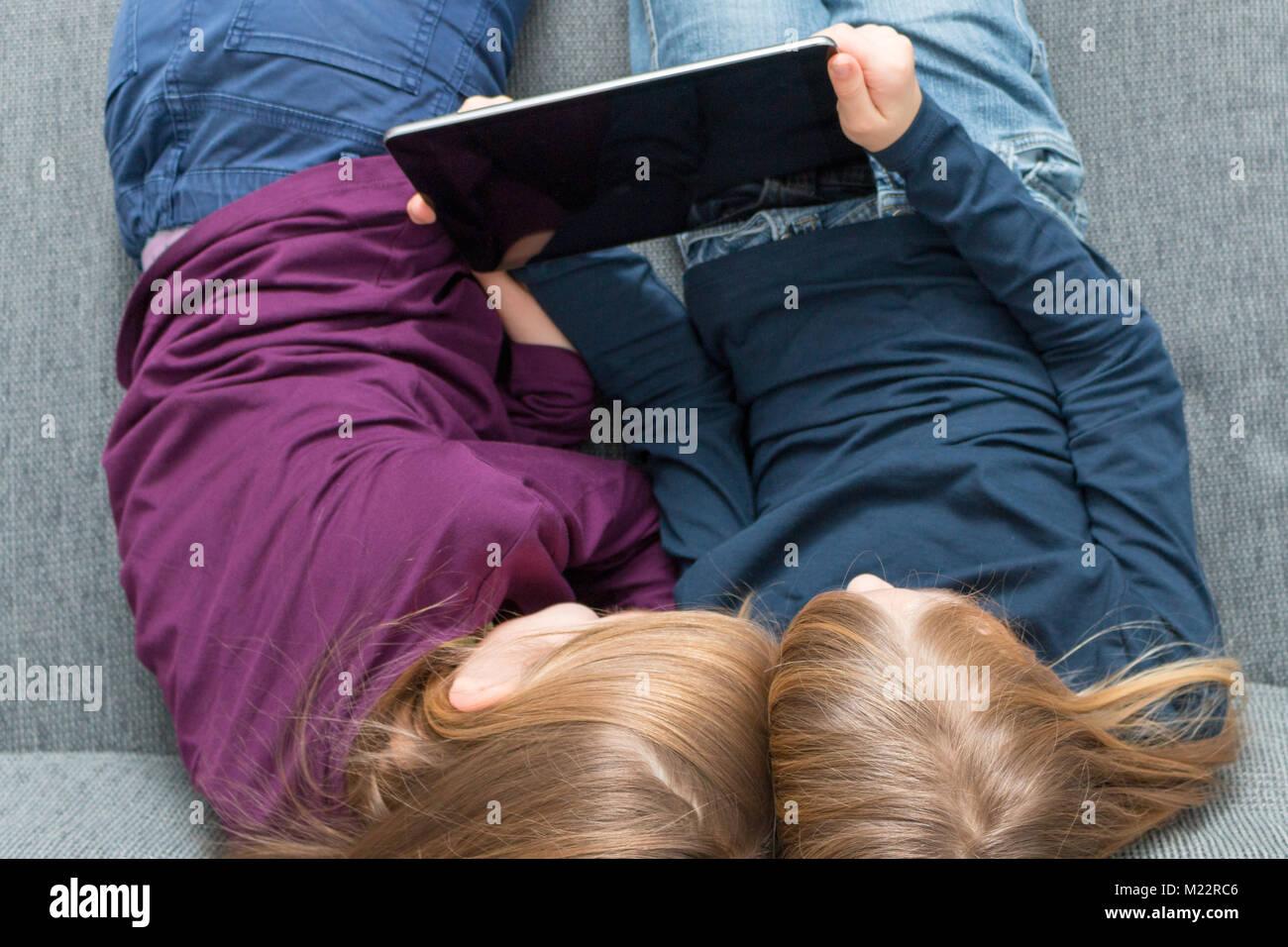 Draufsicht auf  2 Mädchen, die unterhaltsamen Inhalt auf einem Tablet genießen - Stock Image