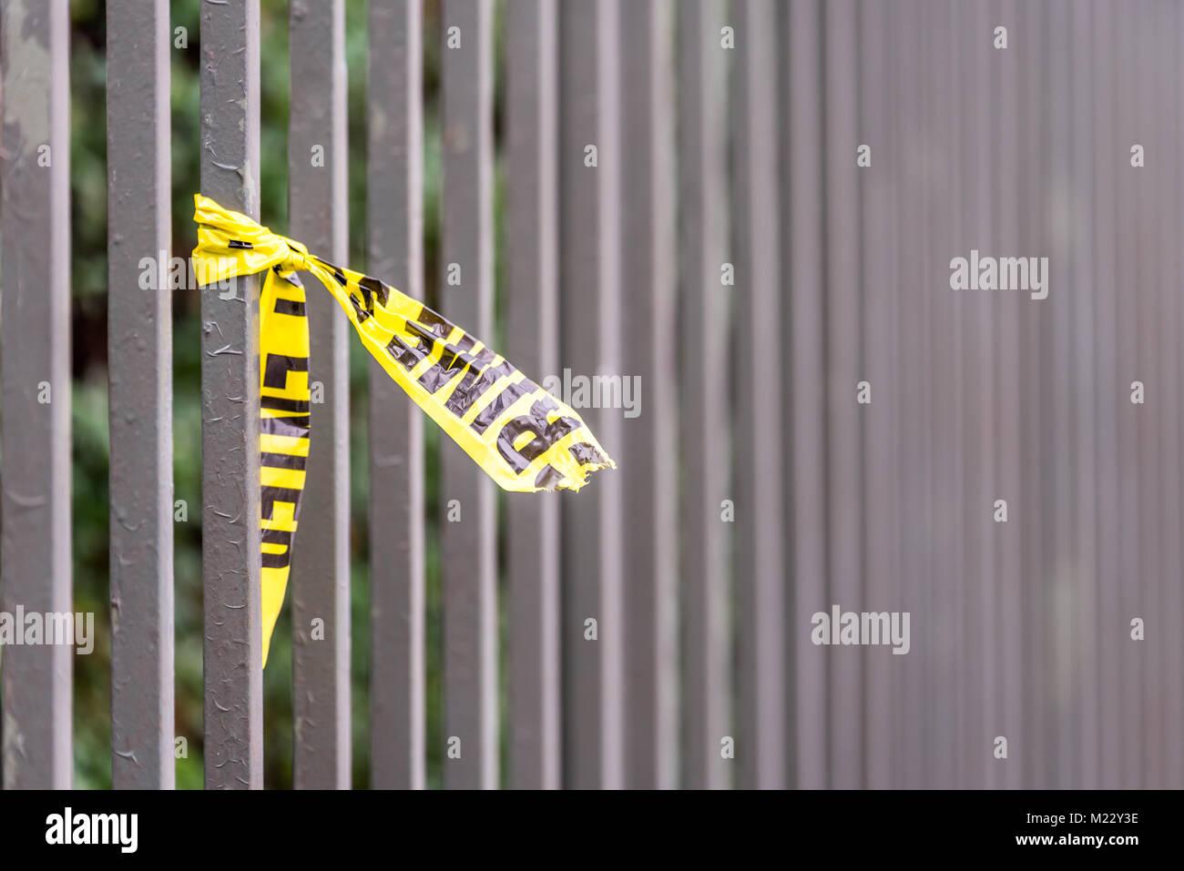 Crime scene border tape peace left on fence in UK Stock Photo