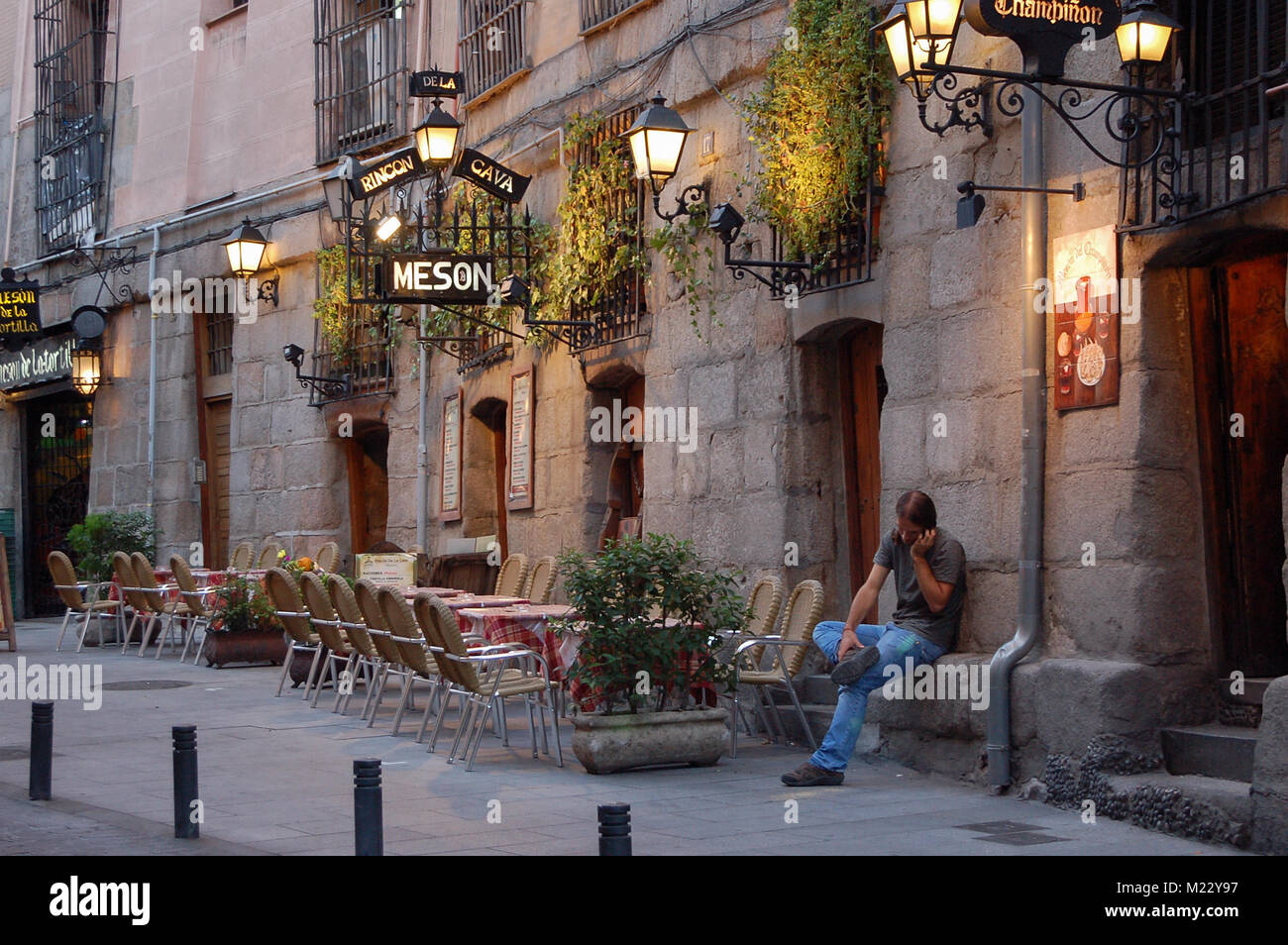 A young man has a call in front of the Meson Rincon de la Cava tapas restaurant off Plaza Mayor - Madrid, Spain - Stock Image