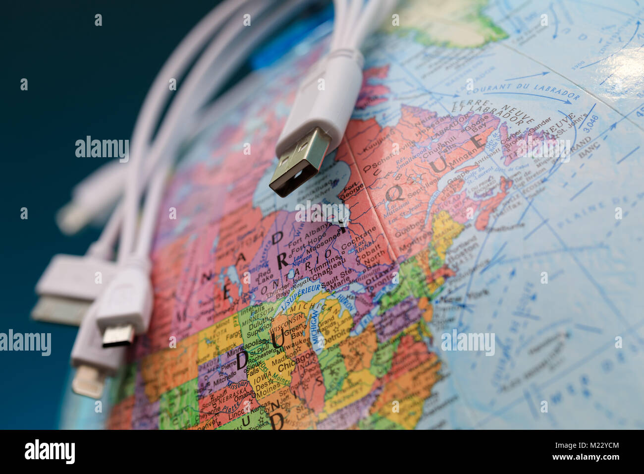 Globe and usb cables (toponymics are written in French). Focus on province of Ontario, Canada. Global communication. - Stock Image