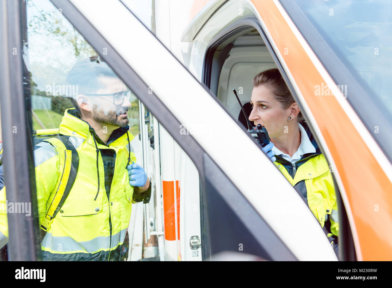 Paramedics in ambulance in radio contact with headquarters - Stock Image