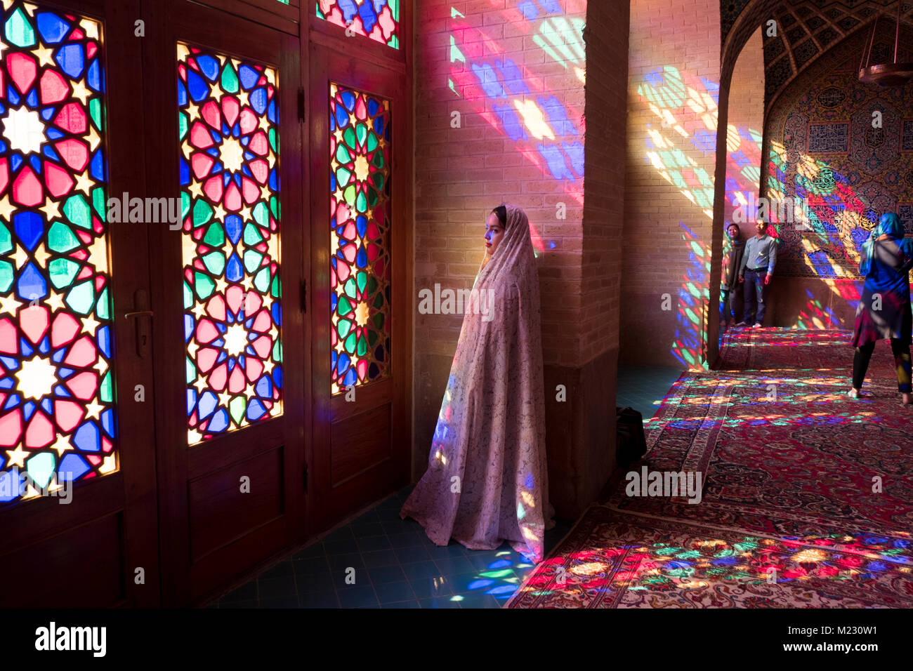 A Tourist stands in the light coming through the stain glass windows of the Nasir al Molk mosque in Shiraz - Stock Image
