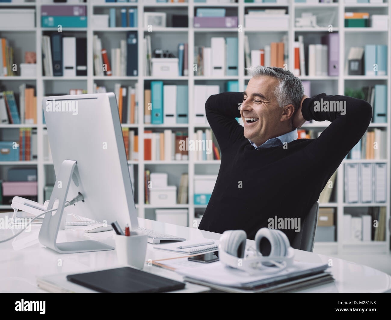 Confident smiling businessman relaxing in his office with hands behind head: successful business and achievement - Stock Image