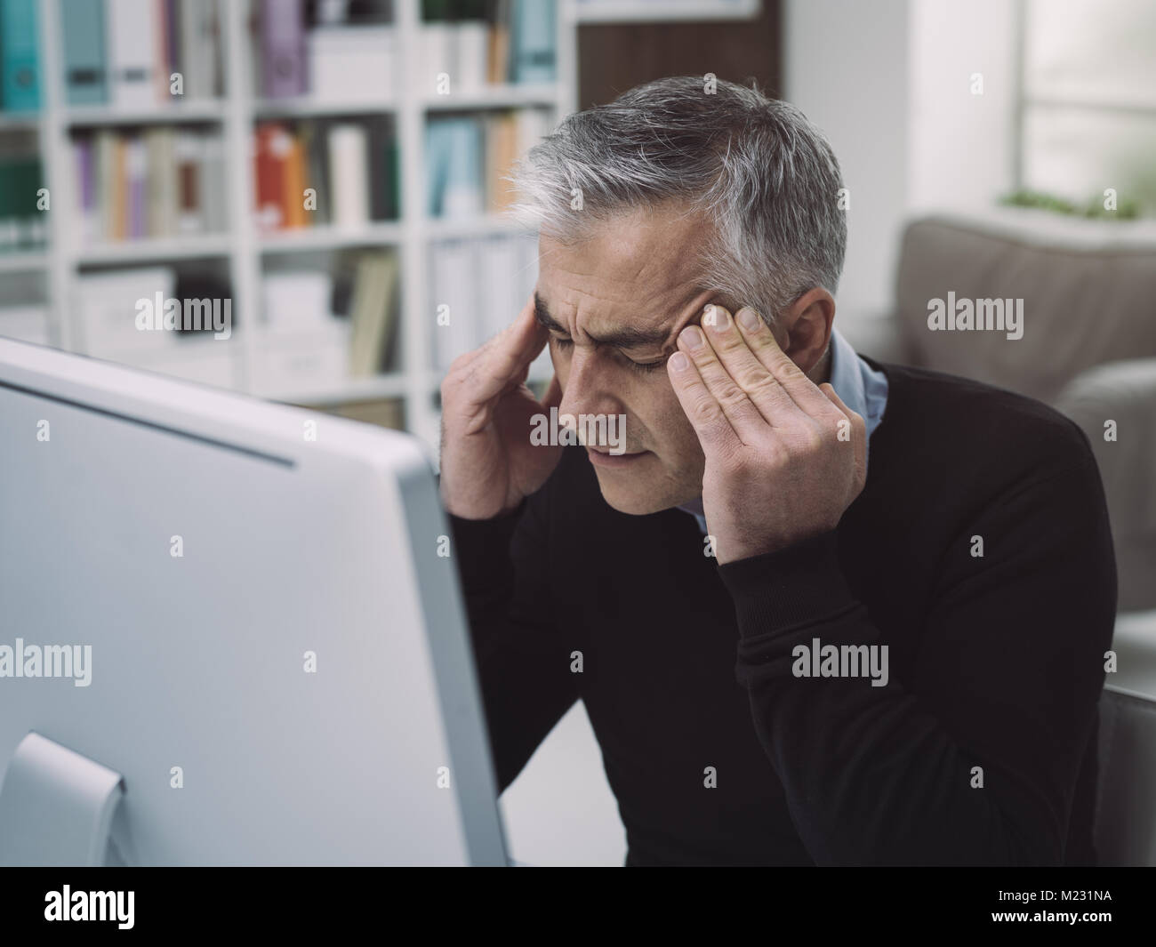 Tired overworked businessman having a bad headache, he is massaging his temples: stress and deadlines concept - Stock Image